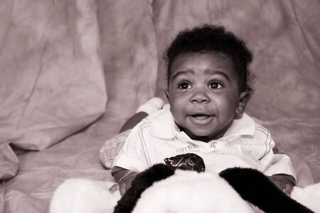 Baby Boy on Tummy Smiling with Stuffed Animal