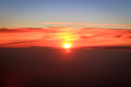 An orange sun rising over the clouds photo