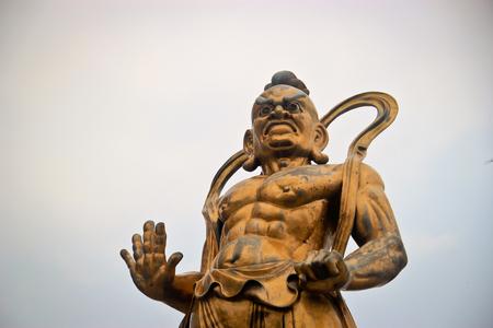 deity: Bronze statue of a Chinese warrior deity against the hazy sky Stock Photo