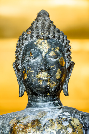 venerate: The ancient metal Buddha statue with gold sheets.
