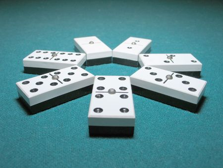 Double Dominoes ordered like a flower on a lighted table Stock Photo