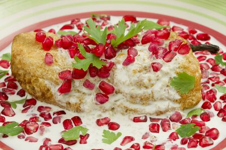 close up food: Chile en Nogada Mexican dish made from a Serrano chile with a fried egg cover, walnut sauce and pomegranate seeds for flavor.