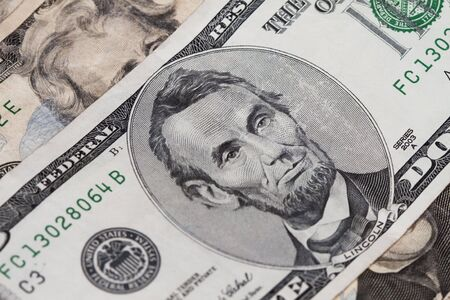 Abraham lincoln in the five dollar bill with two twenties out of focus above and below.
