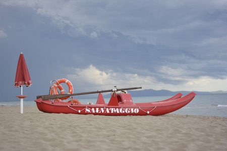 Red rescue boat on the beach with lifebelt and umbrella