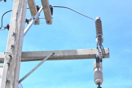 High voltage post against blue sky Stock Photo