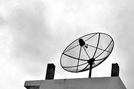 black antenna communication satellite dish over sunset sky in city photo