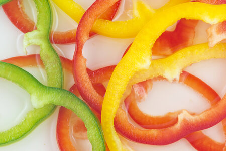 Arrangement of sliced bell peppers on white background Stock Photo