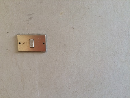 Electrical light switch on the white dirty wall