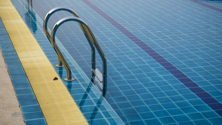 Grab bars ladder in the blue swimming pool Stock Photo