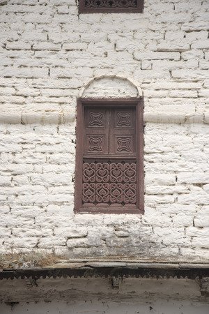 Traditional decorated windows on old stone nepalese house Stock Photo