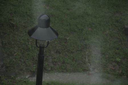 Black electrical light pole in heavy rain Stock Photo