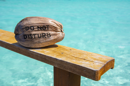 Do not disturb sign on coconut with wonderful beach Stock Photo