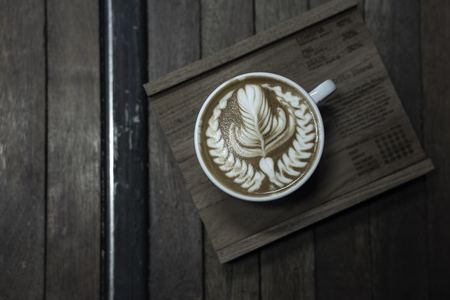 Nice shape of latte art coffee serve on wooden plate Stock Photo