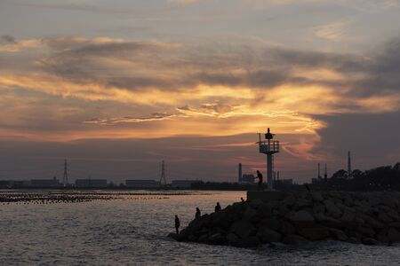 Breakwater rock line with light house against sunset light Stok Fotoğraf