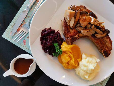 Bistecca di maiale alla griglia servita con fonte barbecue e rete di patate per cena