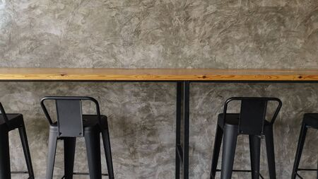 Metal black high chair with wooden table and concrete style wall in cafe