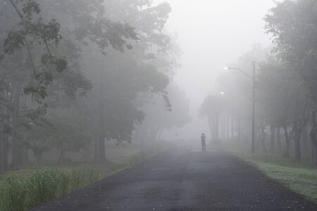 Alone person stand on heavy foggy morning with cold weather and mist also with dusk pollution