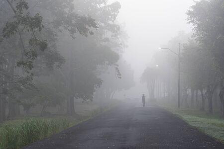 La persona sola sta in piedi in una pesante mattinata nebbiosa con tempo freddo e nebbia anche con inquinamento del crepuscolo Archivio Fotografico