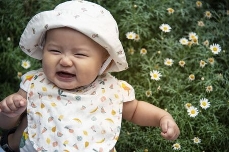 Fat pretty Asian baby infant smiling in background of flowers garden