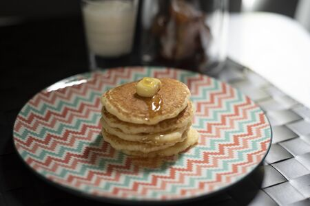 Dessert sweet carb pancake. Multi layer pancake with butter and sweet honey. Vintage pastel plate serve for after lunch break.