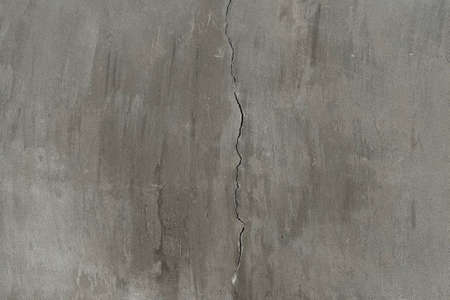 Cracked concrete on grey wall in the middle of frame