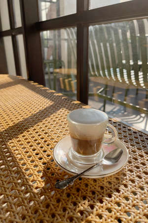 Hard latte coffee shot serve in small shot glass against sunlight from window shade in vintage cafe