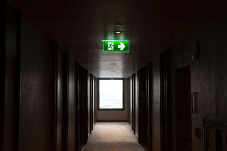 Illuminated green light emergency exit sign in public building for emergency accident and fire case 스톡 콘텐츠
