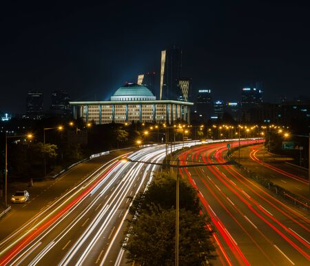 megacity: Traffic blurs along on motorway with the National Assembly in Seoul,South Korea Stock Photo