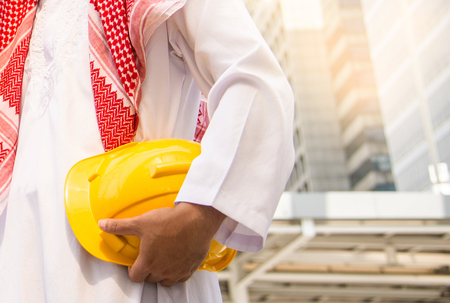 Arab Engineer or Safety officer holding helmet construction or yellow helmet for workers security with city background in construction site.