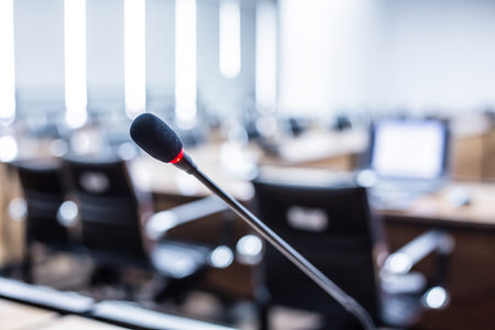 Close up Microphone over the Abstract blurred of conference hall or seminar room background. Stock Photo