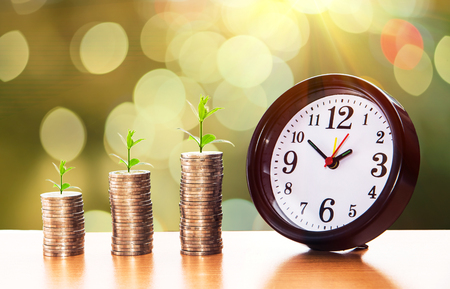 Money Stack and Clock, Business success growing concept, Trees on pile of coins money with clock over sun flare silhouette tone.