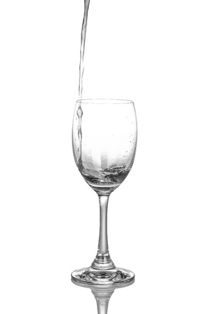 neral water pouring into a glass on a white background. photo