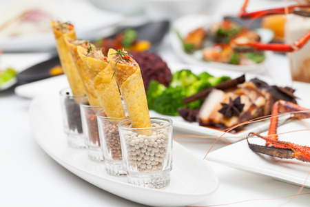 Wrapped in fish in a glass on a white plate. Stock Photo