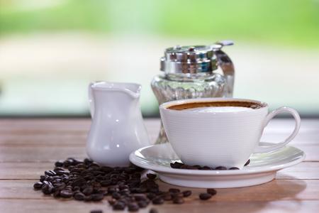 Blanc tasse de café placée par la fenêtre sur un fond vert. Banque d'images