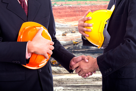 contractor: Business handshake on the background mines.