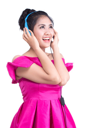 Woman wearing a pink dress listening to music on a white background.