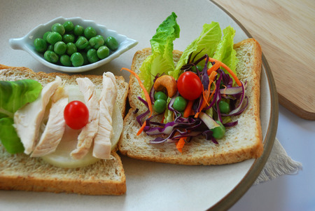 fresh vegetables and chicken on whole grain bread on a plate decorated in delicious photo