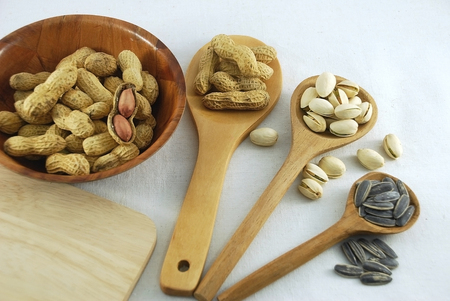monkey nut: peanuts pistachio nuts and sunflower seeds on a wooden ladle are different size and decorate with peanuts in a bowl on calico background Stock Photo