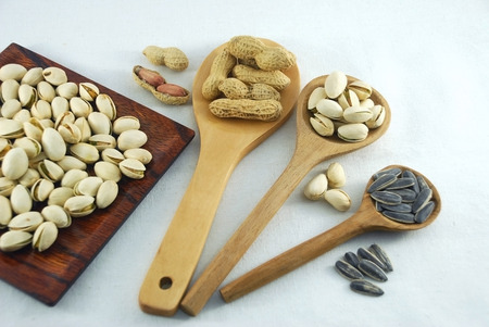 monkey nut: peanuts pistachio nuts and sunflower seeds on a wooden ladle are different size and  wooden square plate and decorate on calico background