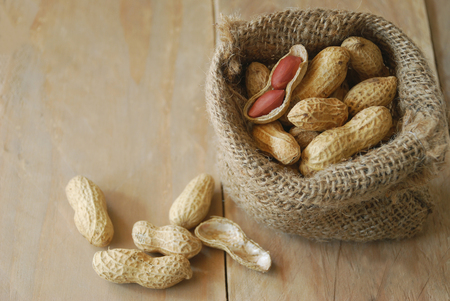 masticate: Peanuts and shelled peanuts decorate in sack bag placed on a wooden background Stock Photo
