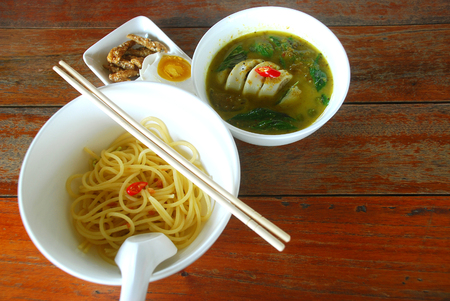 adapted: Green curry squid stuffed with pork. Eat with spaghetti and salted eggs with crispy fried fish. Thailand food dish is adapted. Stock Photo