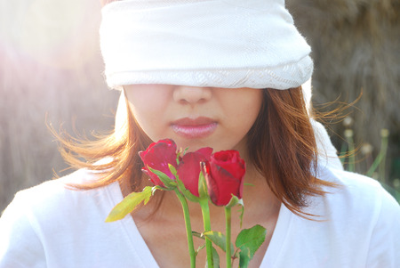 Asian young woman are bind with white scarf on her eyes in the light and flare in sunshine evening. In concept love is blind.