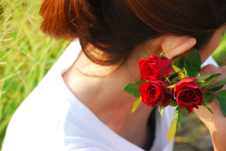 feel affection: Asian young woman show side face, she holding a red roses near her face. She thinking and waiting for someone.