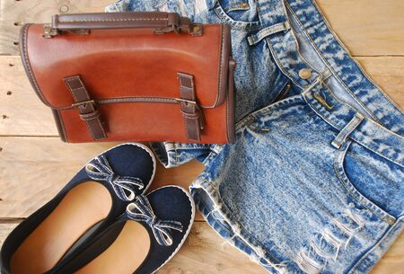 twain: accessories of young women, including a denim shorts, dark blue shoes and brown shoulder bag