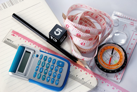 Equipment used in the measurement and calculation, including a compass, ruler, tape measure, calculator, notebook and pencil on white background. Stock Photo