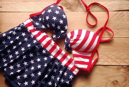personas banandose: traje de baño en estilo del bikini es de rayas bandera americana colocado sobre un fondo de madera