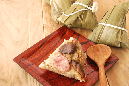 asian ancestry: zongzi is food for the festival ancestor of the chinese people. zongzi made from glutinous rice, salted egg, sausage and dried shrimp wrapped in bamboo leaves were then steamed. Stock Photo