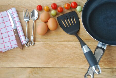 flipper: kitchenware are including frying pan, flipper used in frying, spoon, fork, knife, napkins, eggs and fresh tomatoes, placed on a wooden background in top view. Stock Photo