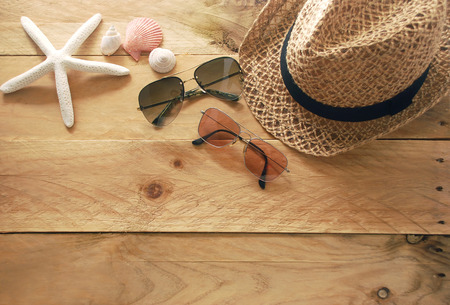 sea shells on beach: brown hat and two sunglasses with shells and starfish are decorated on a wooden background in top view Stock Photo