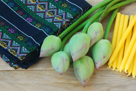 lent: Fresh green lotus bud for worship with a yellow candles and colorful local fabrics in buddhist sabbath. Stock Photo